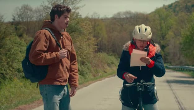 Scene where Paul Munsky, played by Daniel Diemer, watches Ellie Chu, played by Leah Lewis, read a handwritten note while hunched over her bike