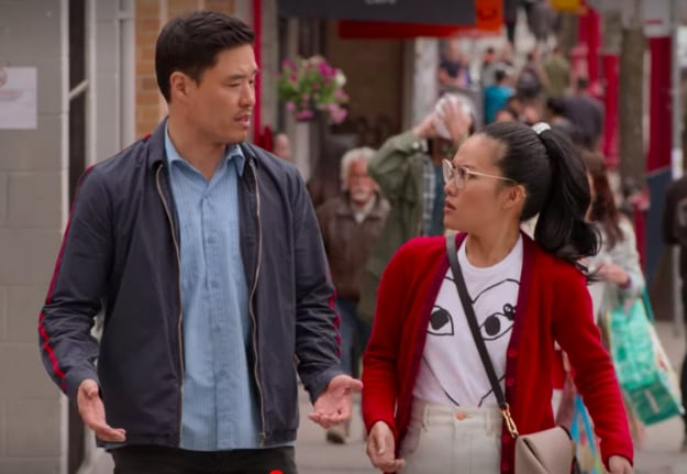 Scene where Sasha Tran, played by Ali Wong, and Marcus Kim, played by Randall Park, look at each other in confusion while walking down a crowded street