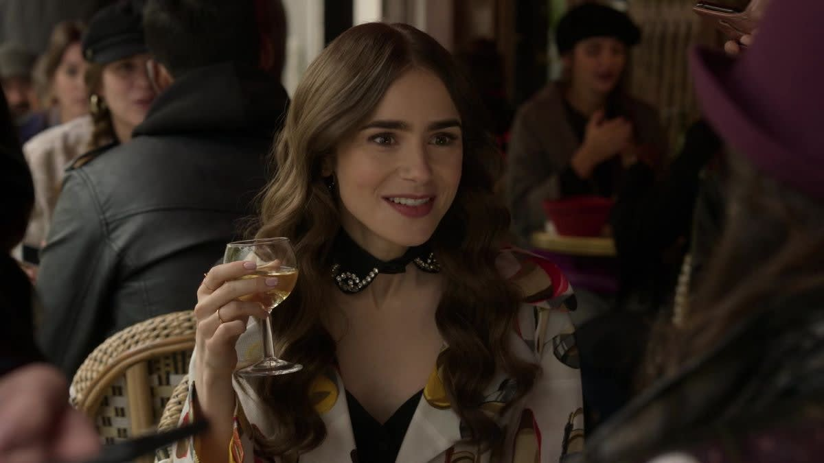 """Lily Collins holds up a glass of wine as Emily in """"Emily in Paris"""""""
