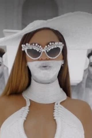 Beyonce is wearing an all-white mask, dress, hat, and sunglasses with beads around the frame