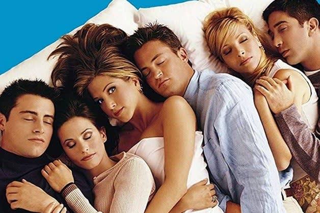 """Imagem do elenco de """"Friends"""" deitado em uma cama, todos abraçados."""