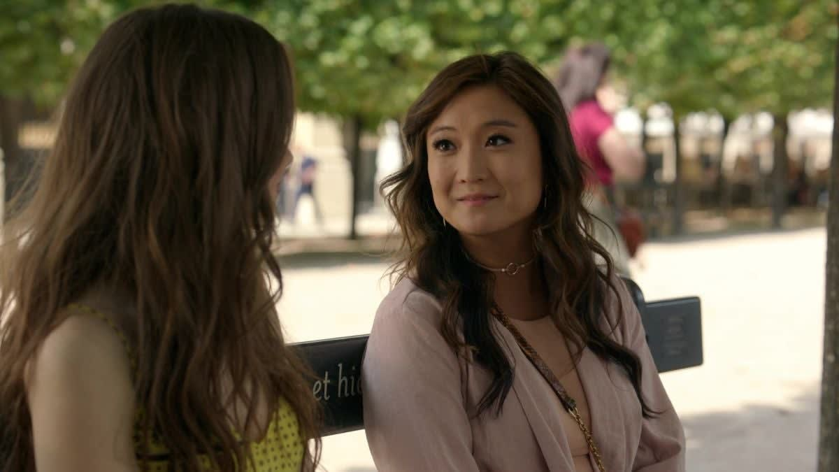 """Ashley Park sits on a bench as Mindy in """"Emily in Paris"""""""