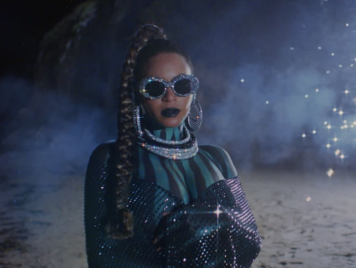 Beyonce is posing wearing bejeweled sunglasses, standing in front of fog