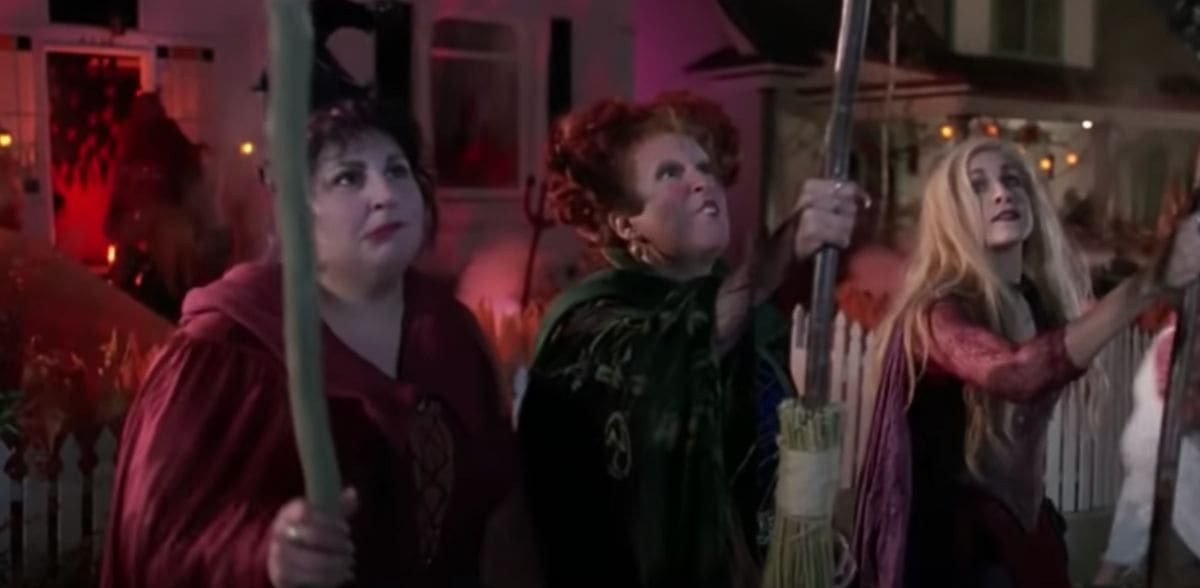 Three witches are holding up their broom while making a silly face