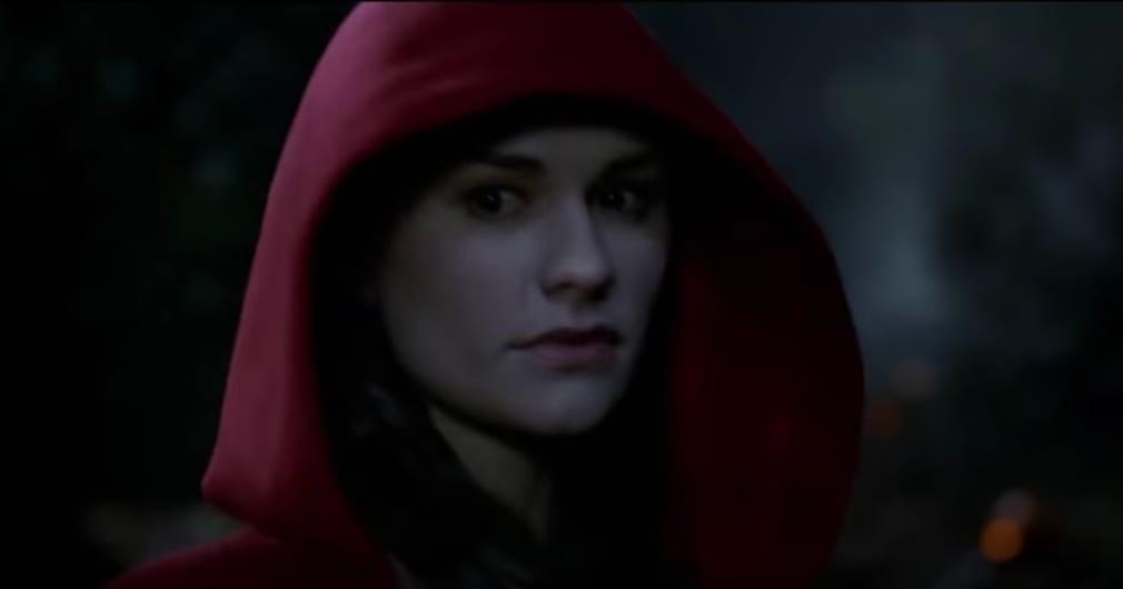 A woman is standing in a dark woods wearing a hood