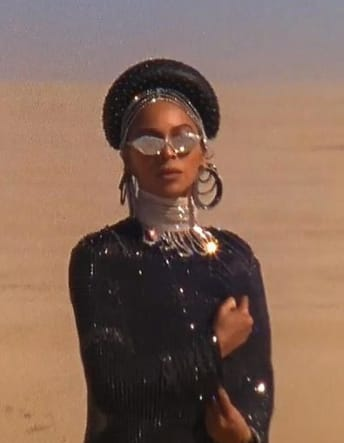 Beyonce is in a desert with chain necklaces and diamond sunglasses