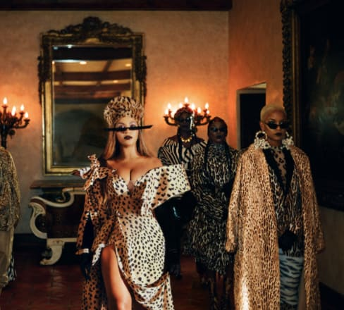 Beyonce is wearing a leopard print dress with large, linear-like sunglasses