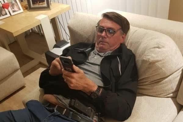 Bolsonaro de óculos sentado no sofá olhando o celular naquela clássica postura de tiozão