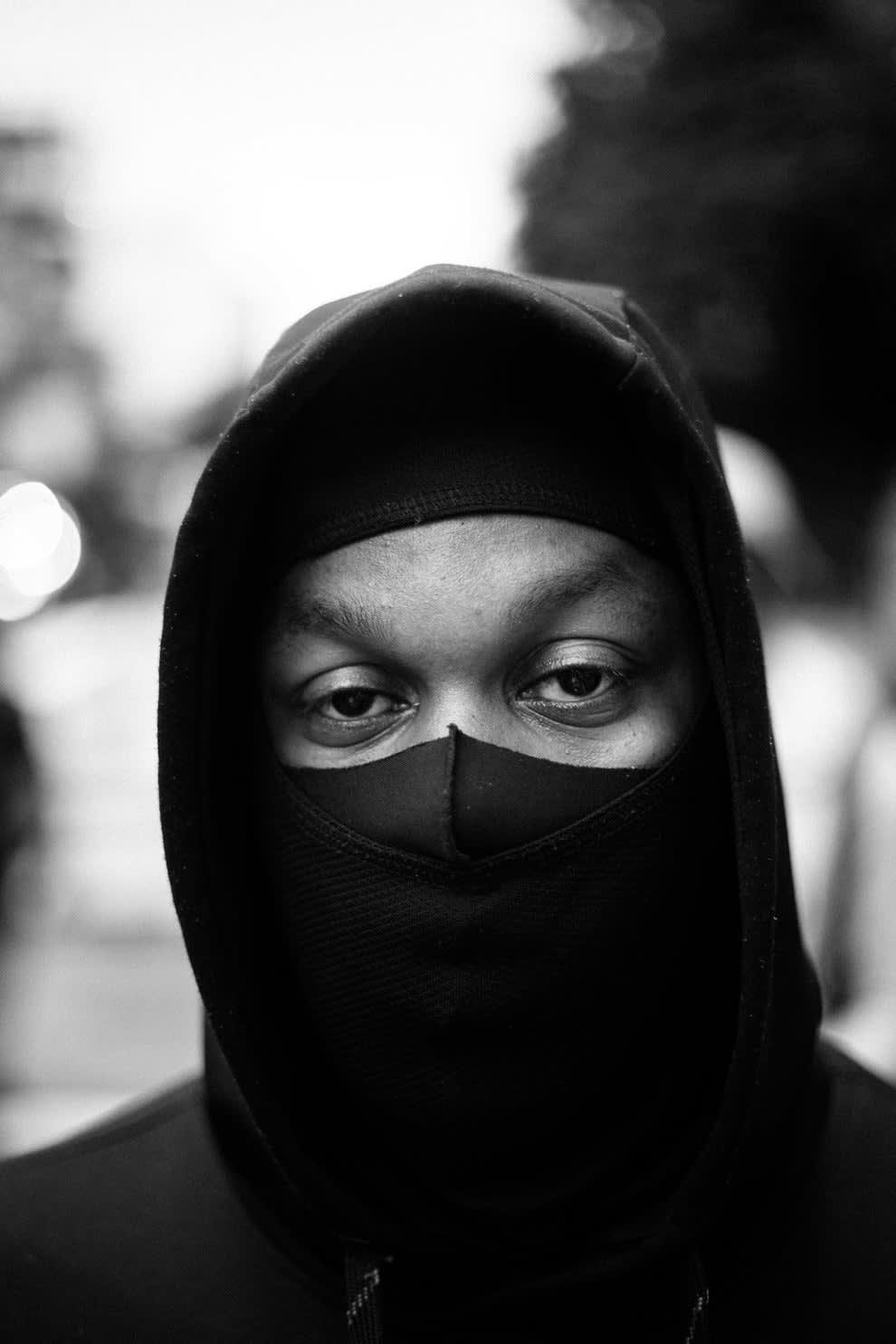 Homem negro usando máscara e capuz preto, olhando para a câmera.