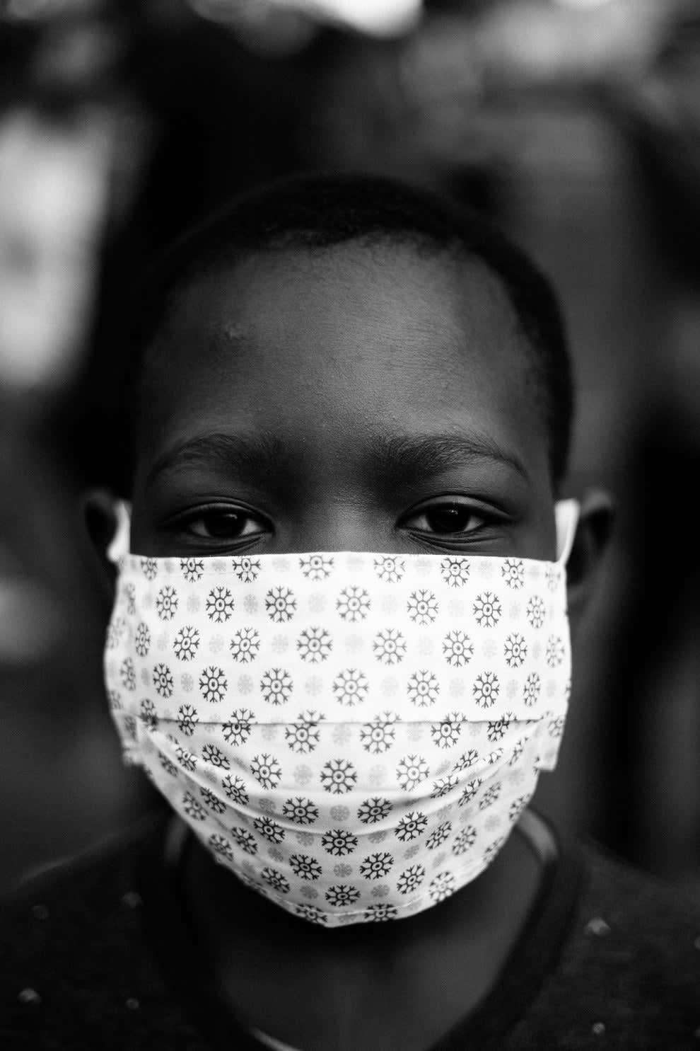 Rosto em close de jovem negro com máscara branca olhando na direção da foto.