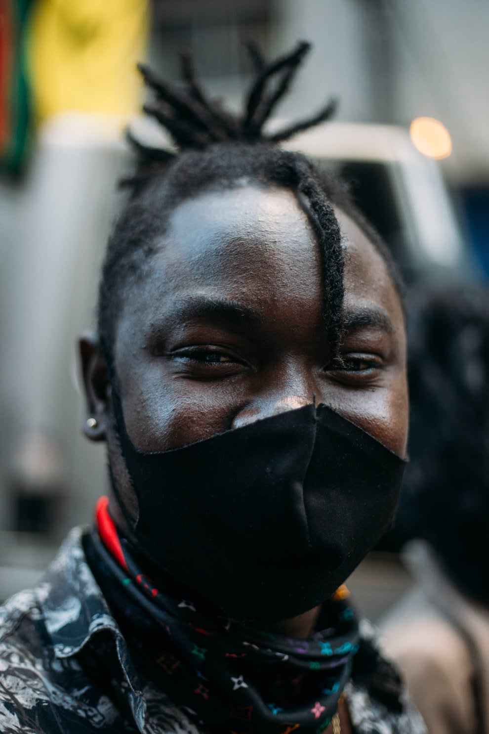 Homem jovem negro usando máscara preta e dreadlocks curtos.