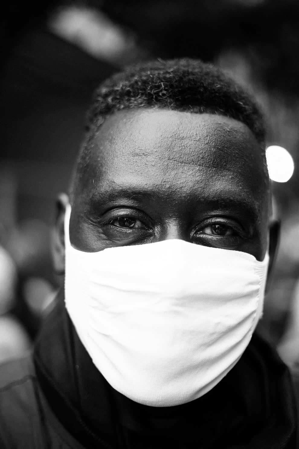 Homem negro usando máscara branca e olhando para a câmera,