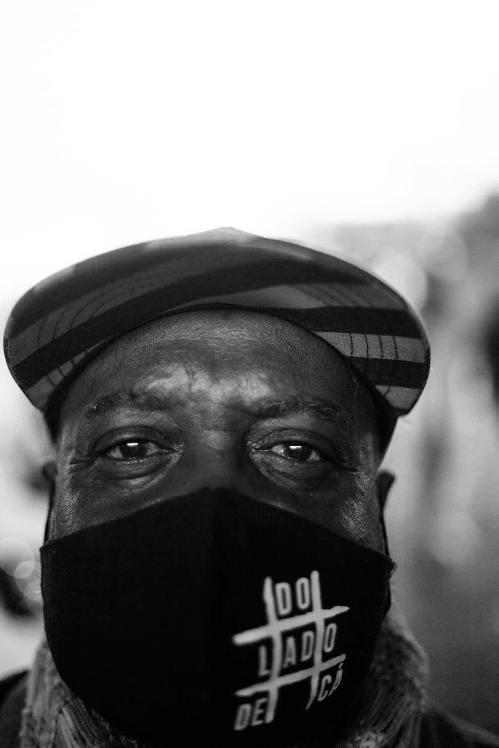 Rosto de homem negro com máscara preta e boné.