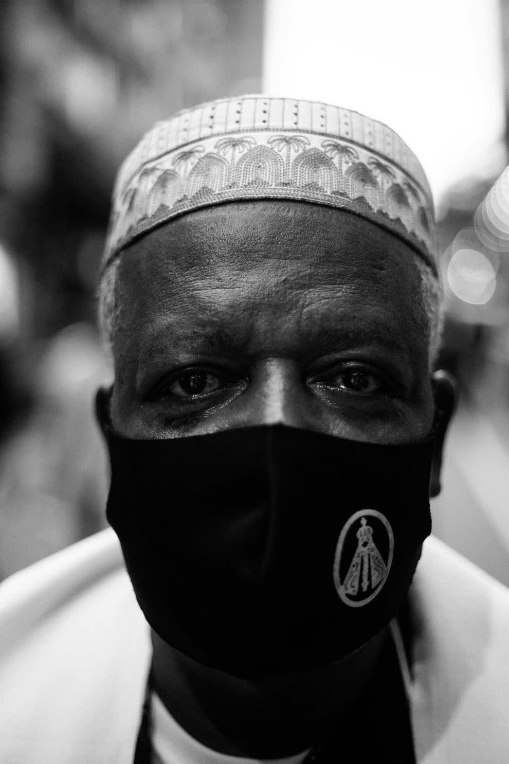 Rosto de homem negro usando chapéu branco com estampa afro e máscara preta com estampa de Nossa Senhora Aparecida.