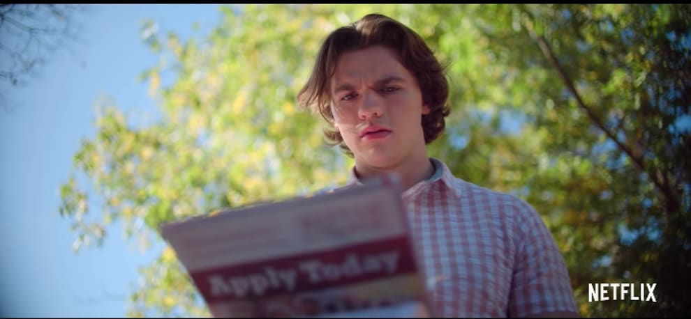 """Joel Courtney as Lee Flynn looking at a college pamphlet in """"The Kissing Booth 2."""""""