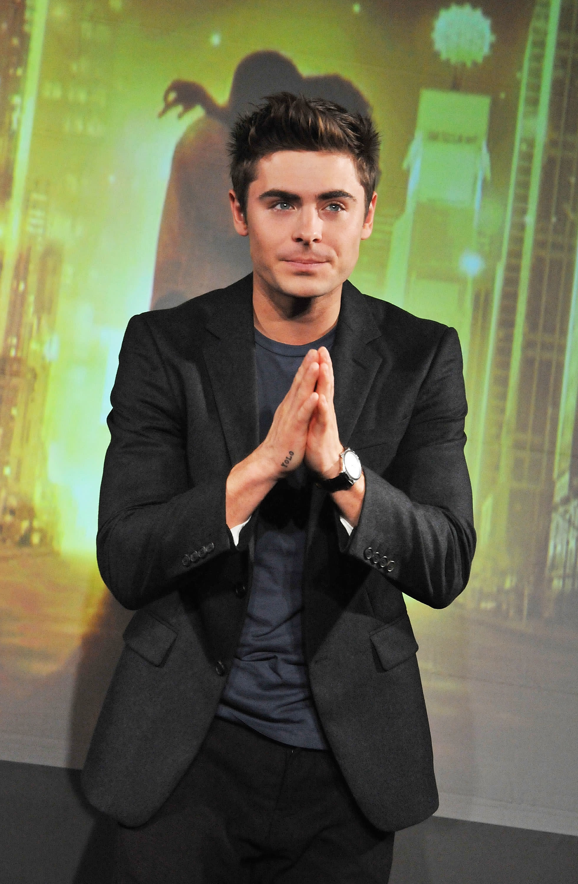 Zac Efron with his hands together
