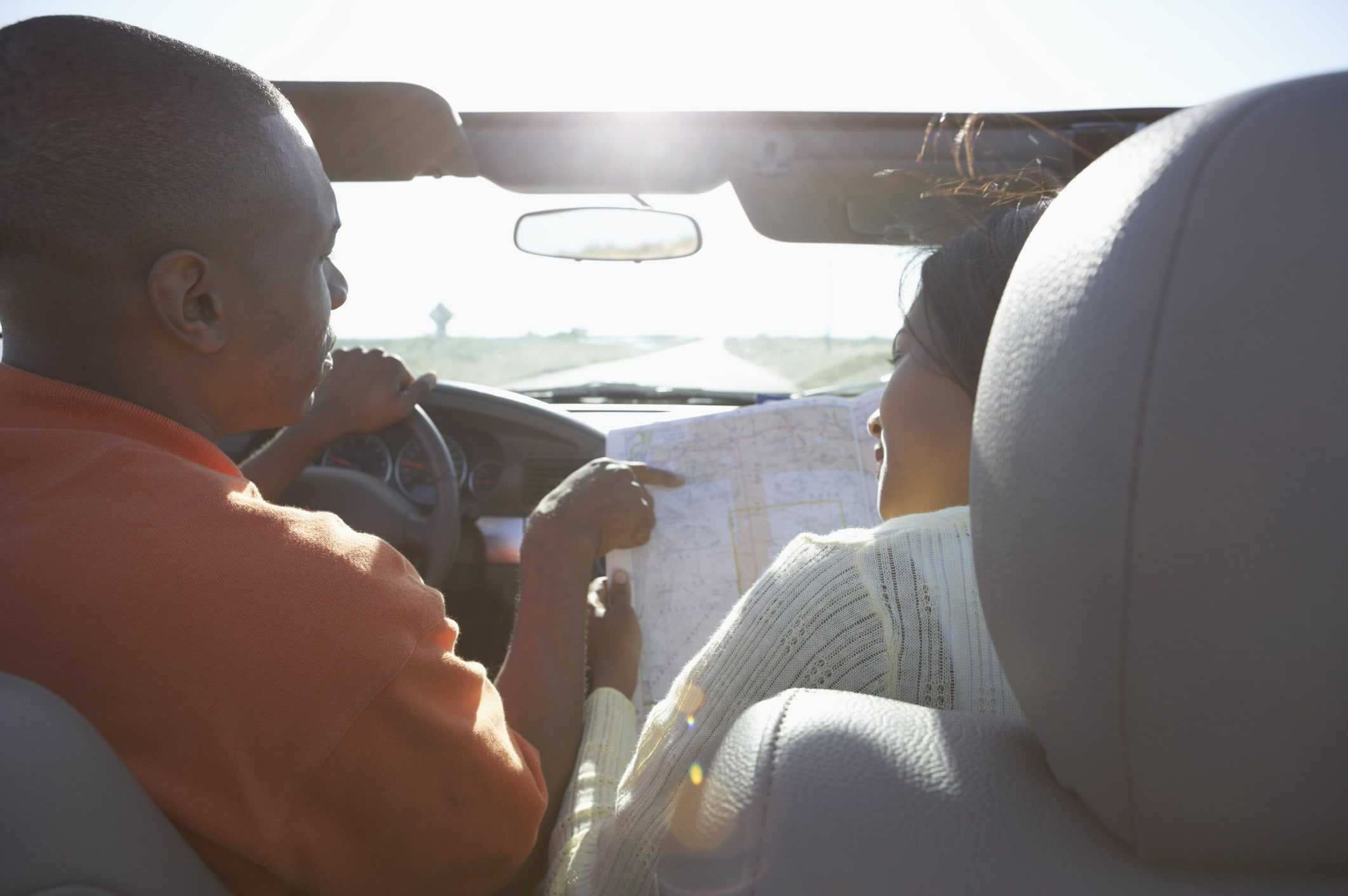 A man and a woman in a car driving and looking at a map