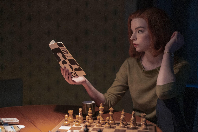 Beth lendo um livro sentada em frente a um tabuleiro de xadrez