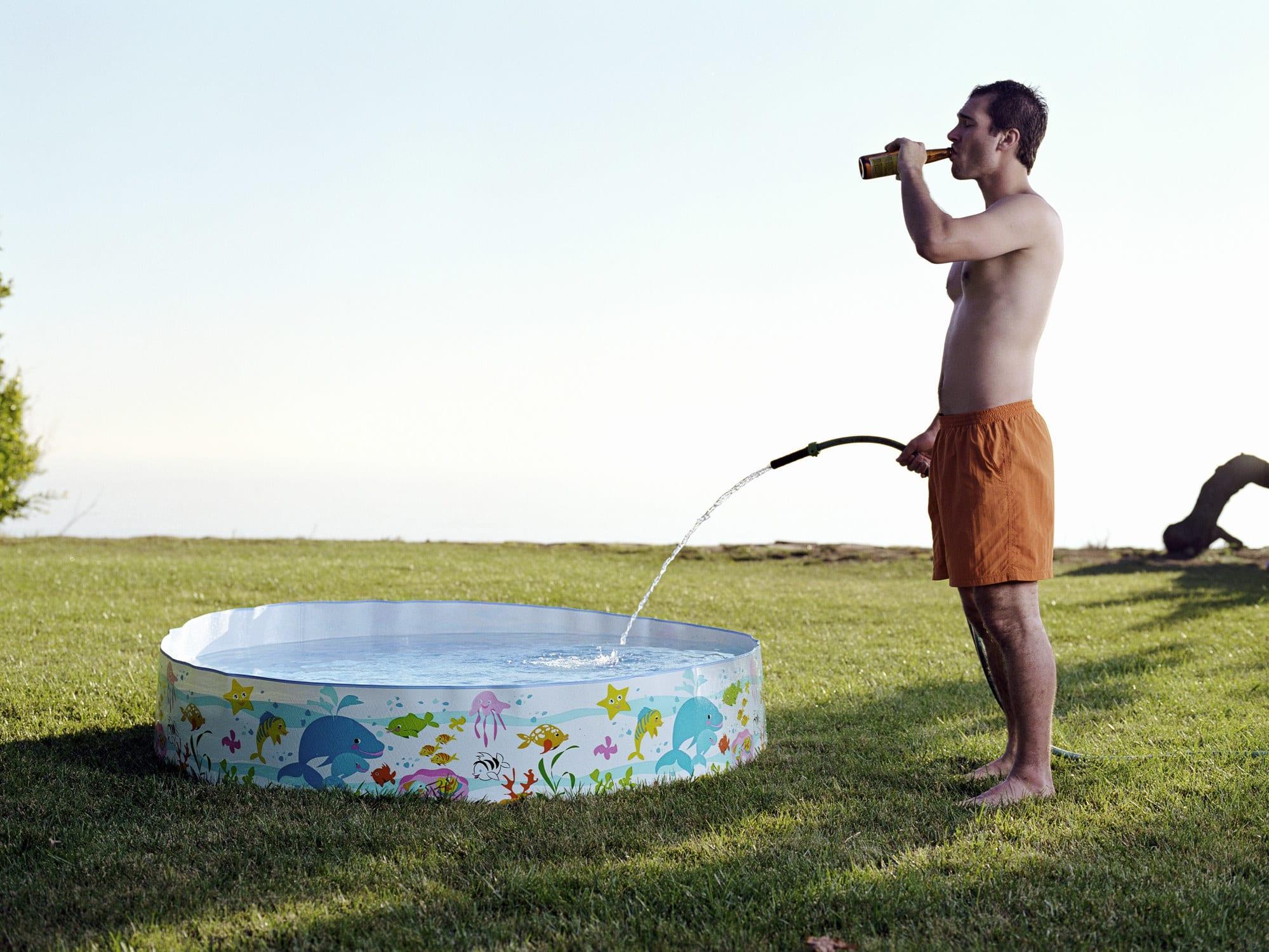 homem segurando uma mangueira na altura do quadril, enchendo uma piscina infantil