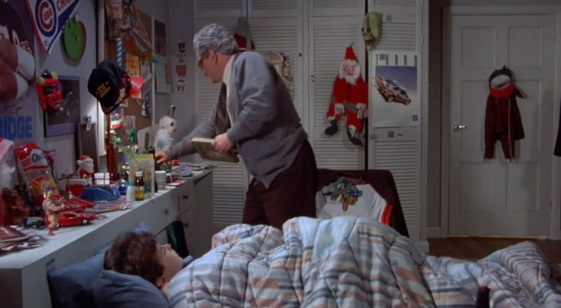 The boy lies in bed and the grandfather stands next to it holding a book in The Princess Bride