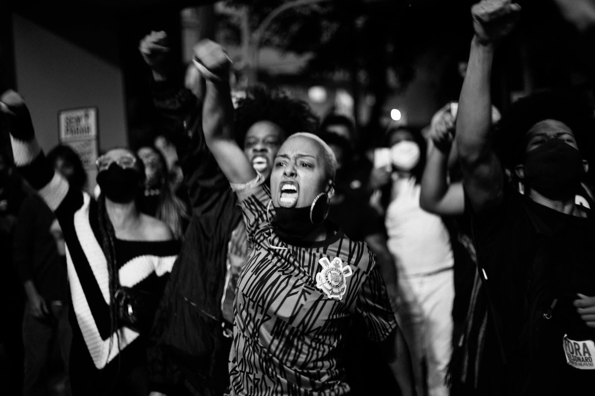 Cena de protesto com pessoas com braços erguidos, uma mulher em primeiro plano vestindo camiseta com estampa de pixo, brincos de argola, com bandana no pescoço, gritando com braço erguido.