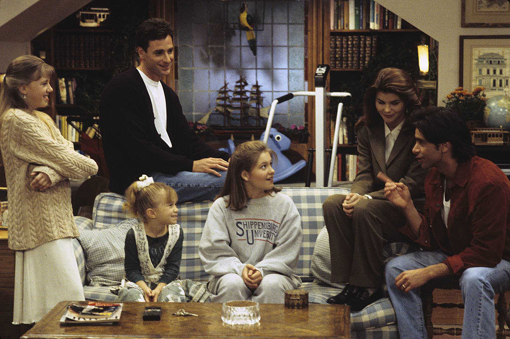 The Tanner family sitting on a plaid couch