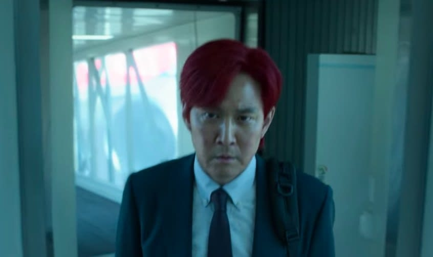 A red-haired Gi-hun walks out of an airport tunnel with a determined look on his face