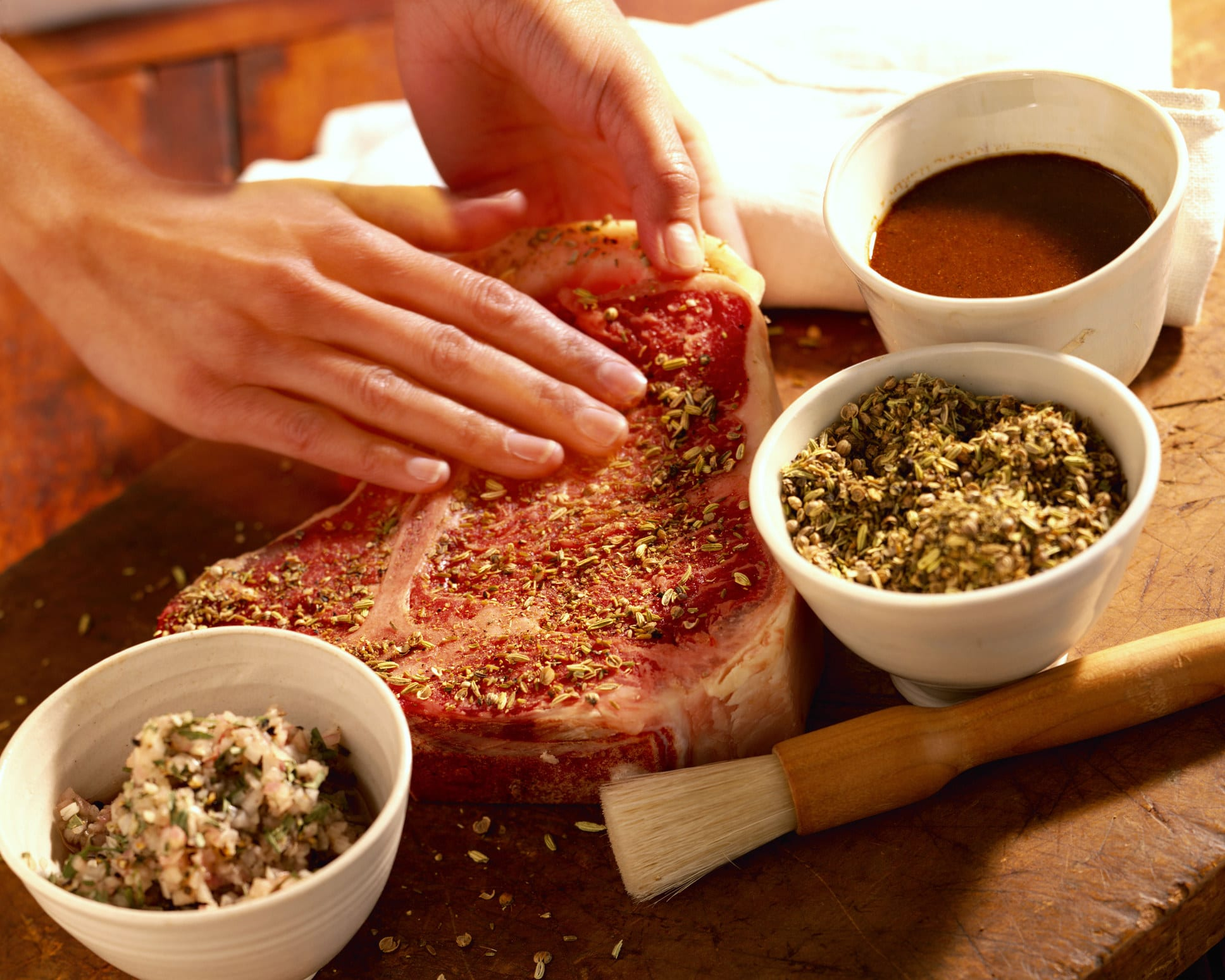 Hands seasoning a steak with herbs.