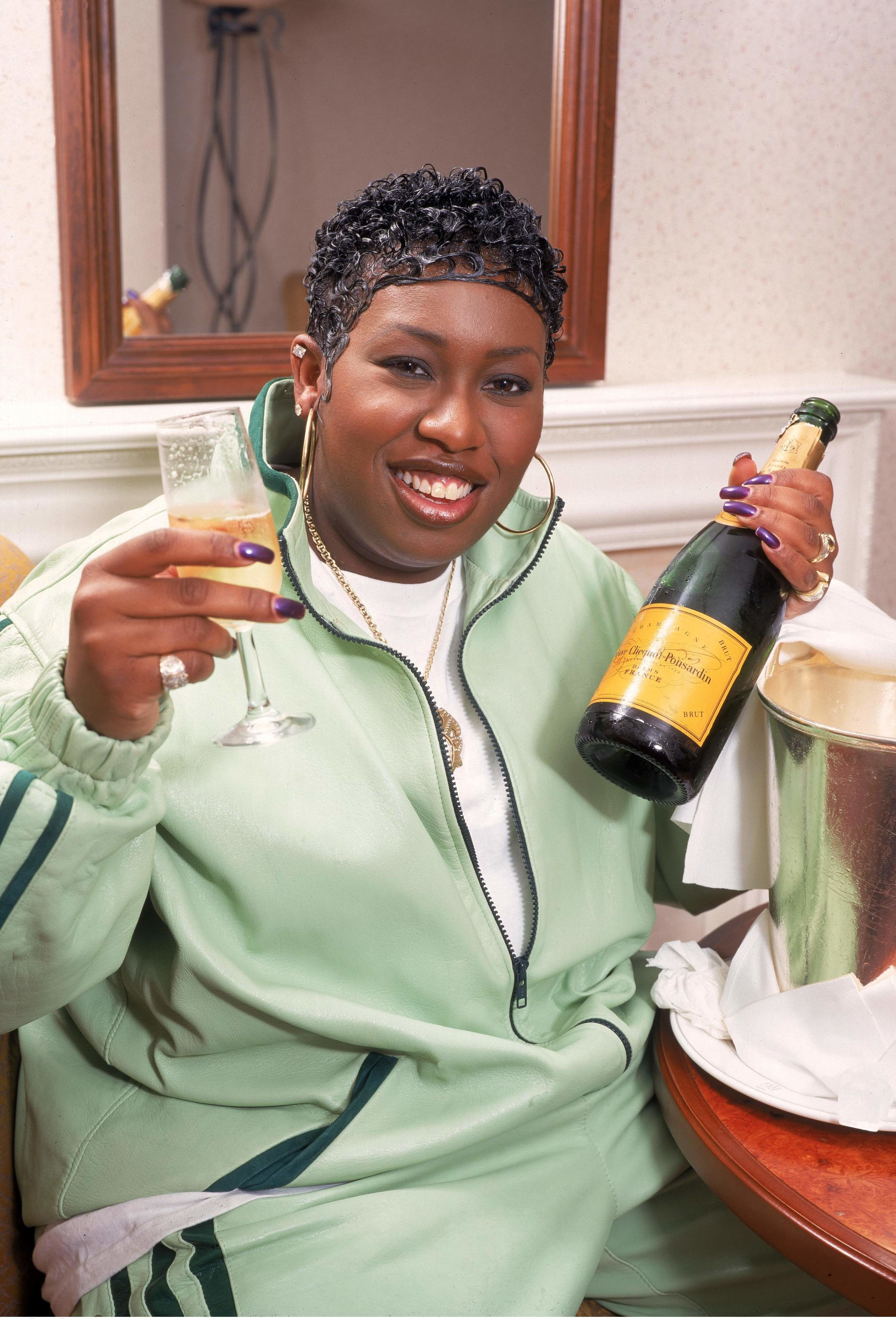 Elliott posing with champagne in 1998