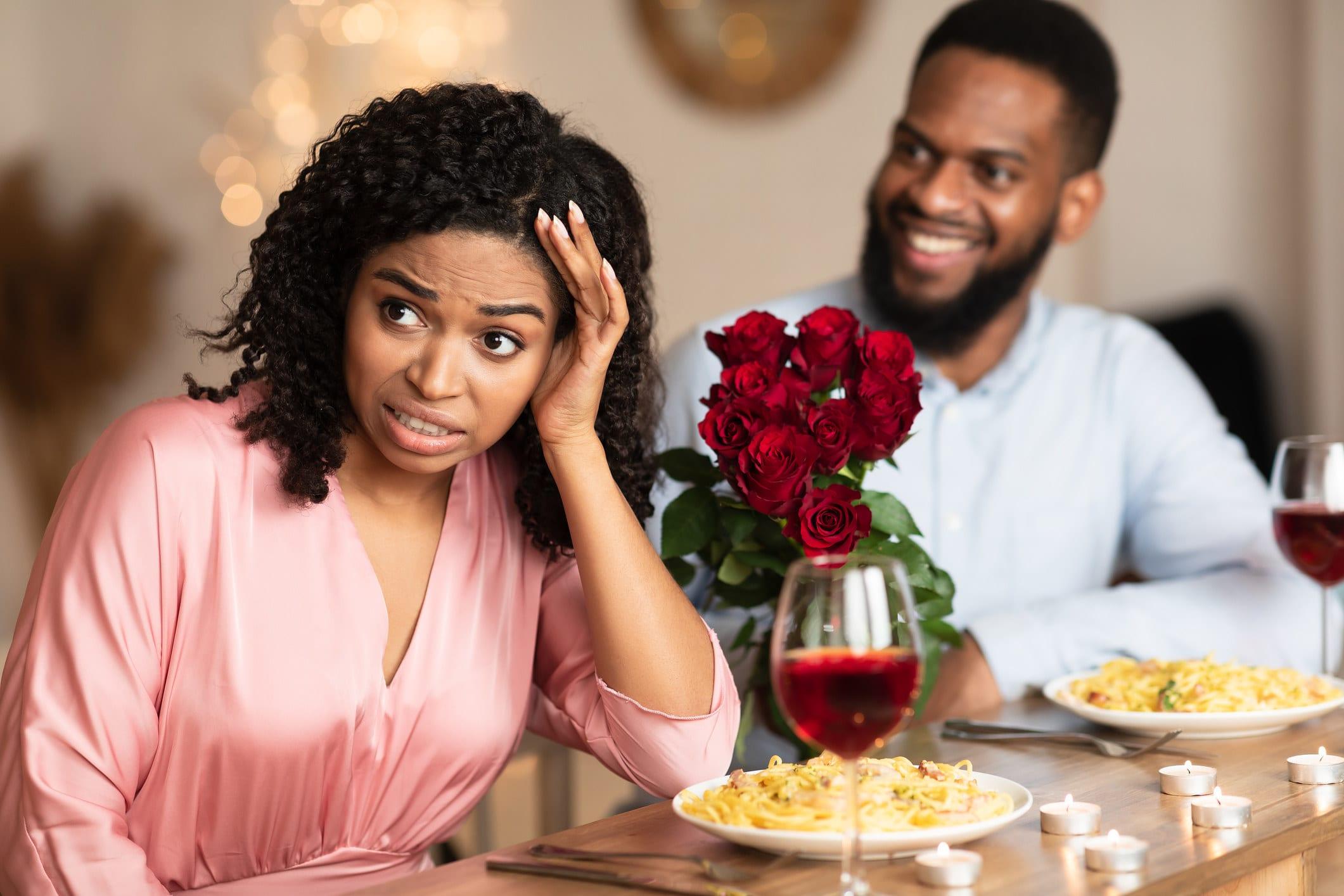 mulher com expressão preocupada de costas para homem sorridente