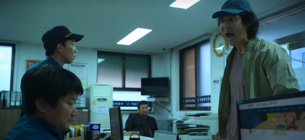 Gi-hun yells at a police officer sitting opposite him in a police station