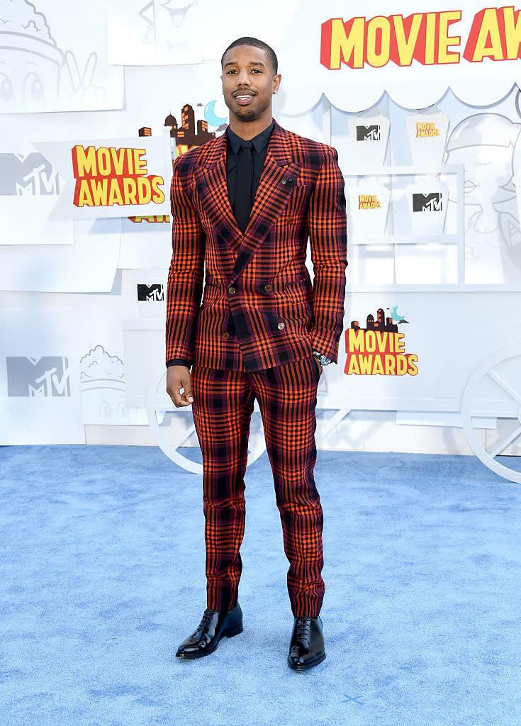 Michael B. Jordan vestindo um terno xadrez vermelho e preto, e a calça segue o mesmo padrão.