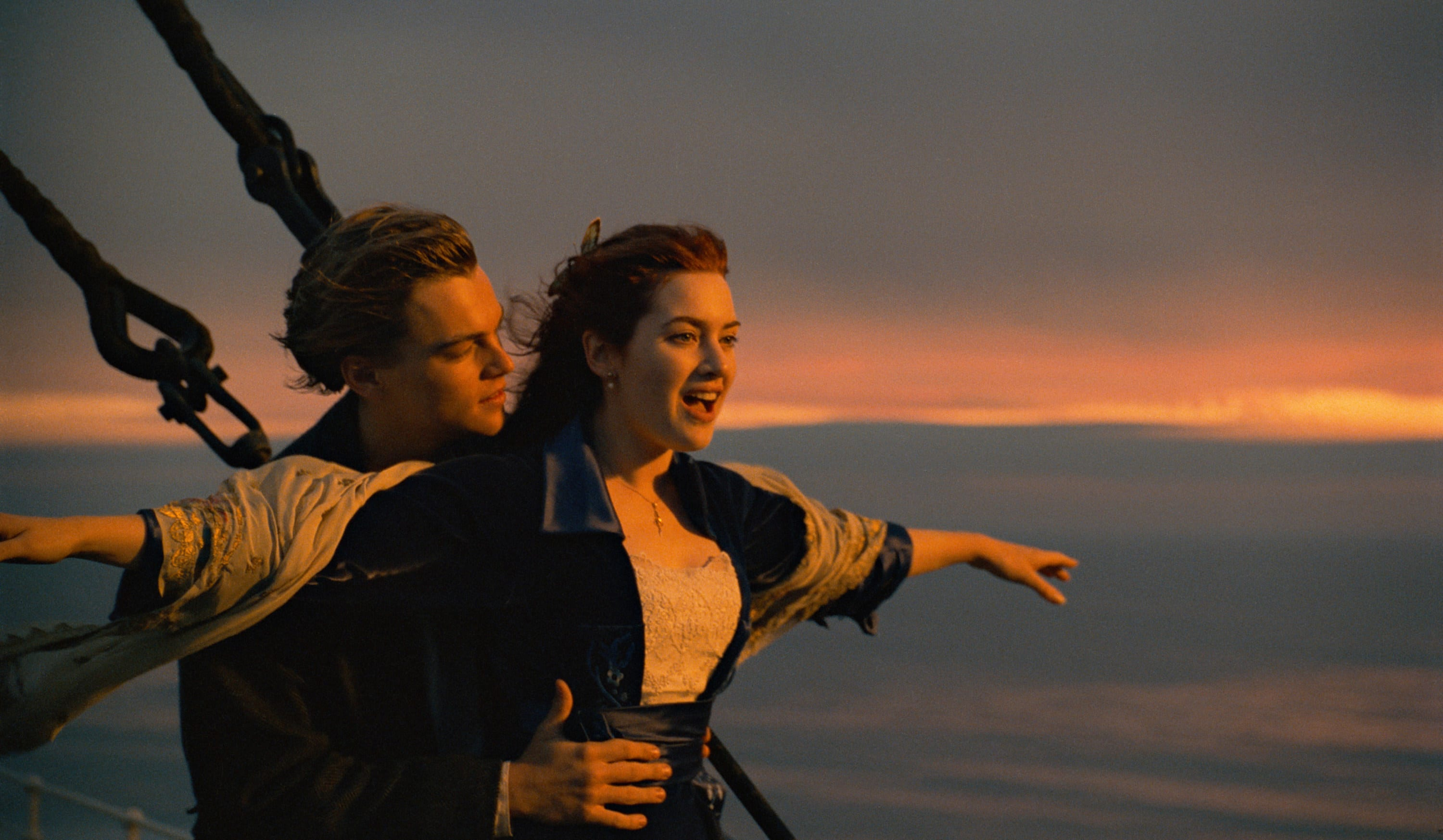 Leo holding Kate Winslet as she spreads her arms open at the front of the Titanic
