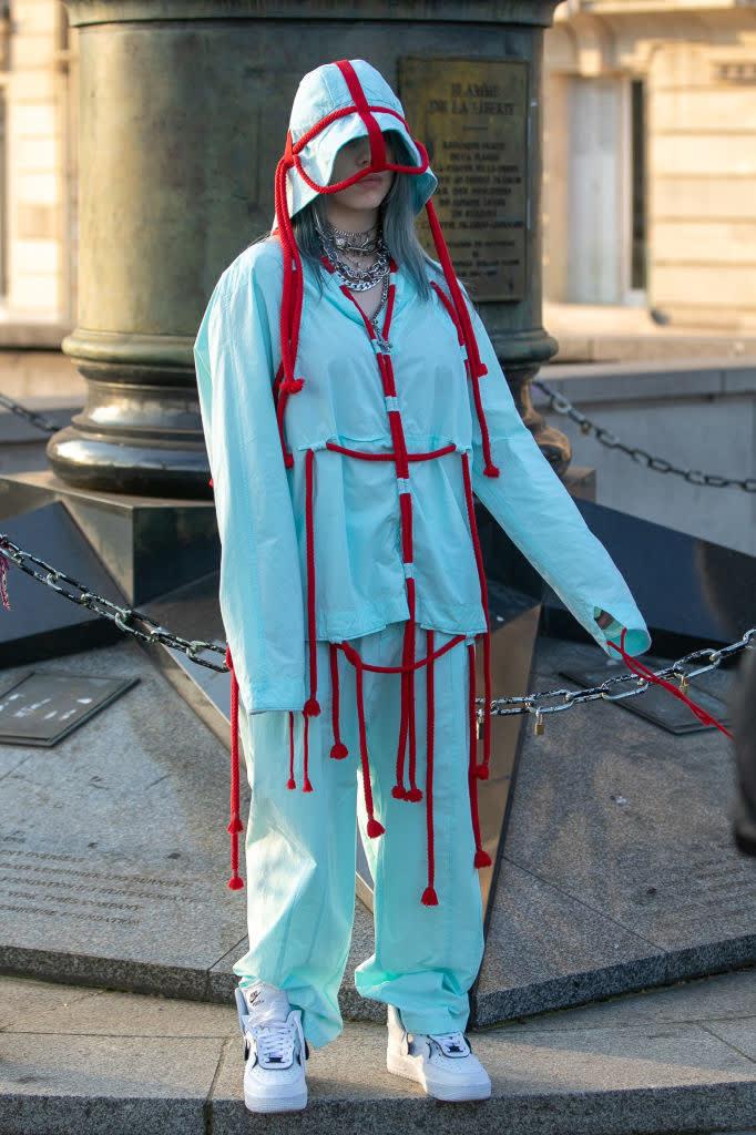 Billie com um conjunto azul e cordas vermelhas penduradas