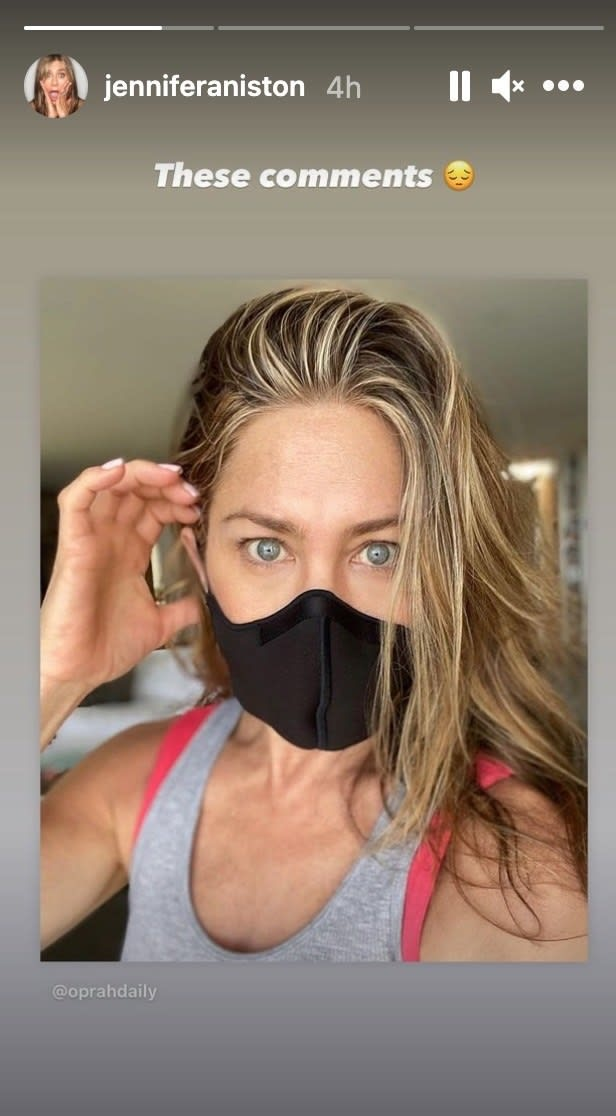 Aniston holds her hand to her ear while wearing a mask