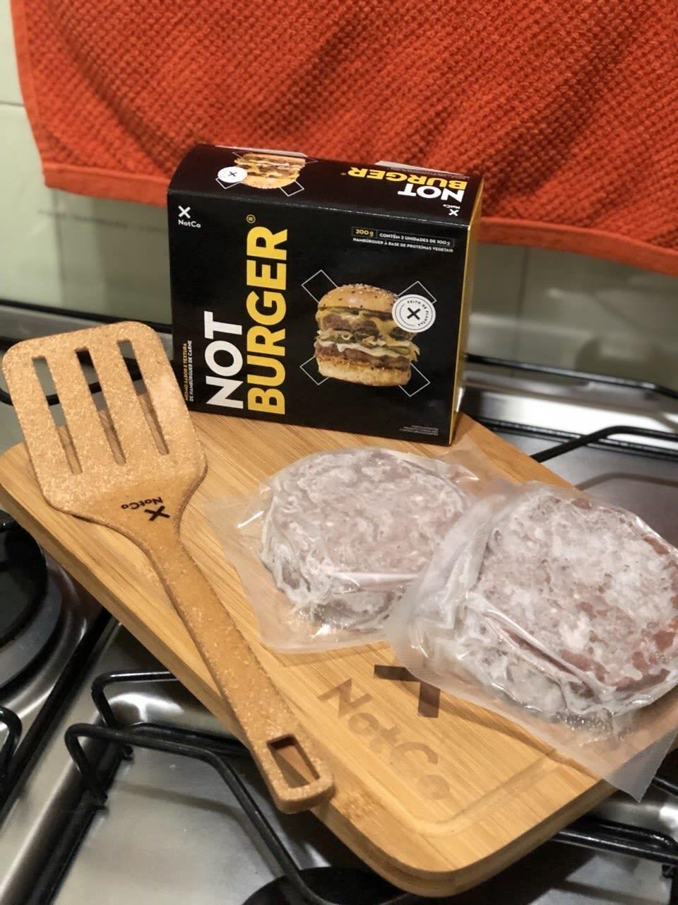 Foto de dois hambúrgueres congelados embalados em um plástico transparente, colocados em cima de uma tábua de madeira com o logo da NotCo. Ao lado dos hambúrgueres está a embalagem do produto e uma espátula também da marca.