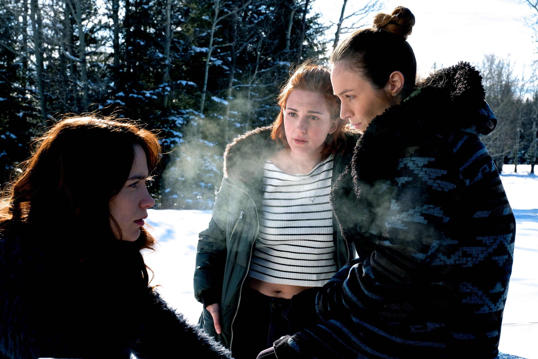Imagem mostra três personagens da série Wynonna Earp em um campo coberto de neve.