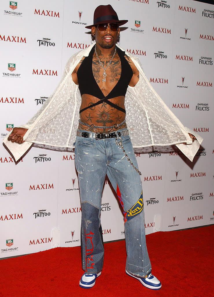 Dennis com um top preto, jeans e uma camisa aberta de rendas