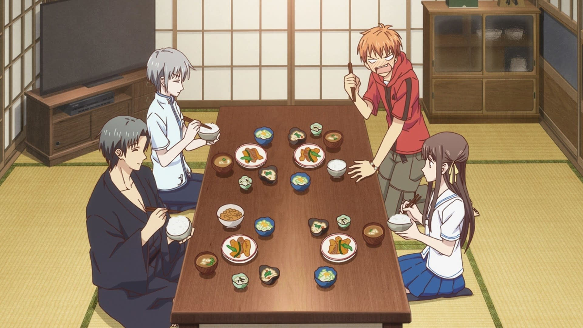 A group of characters eating dinner on a low dining table; they are sitting down with their knees folded or crossed