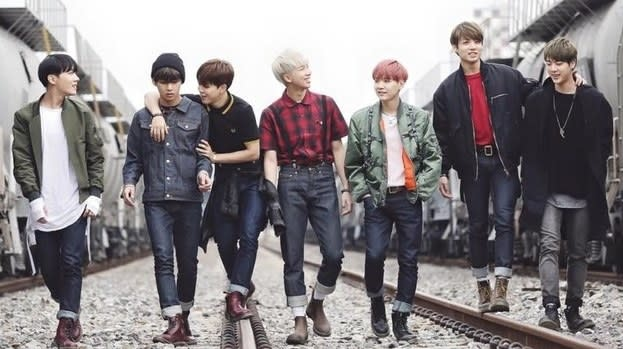 BTS walk in a line along train tracks; they wear casual clothes