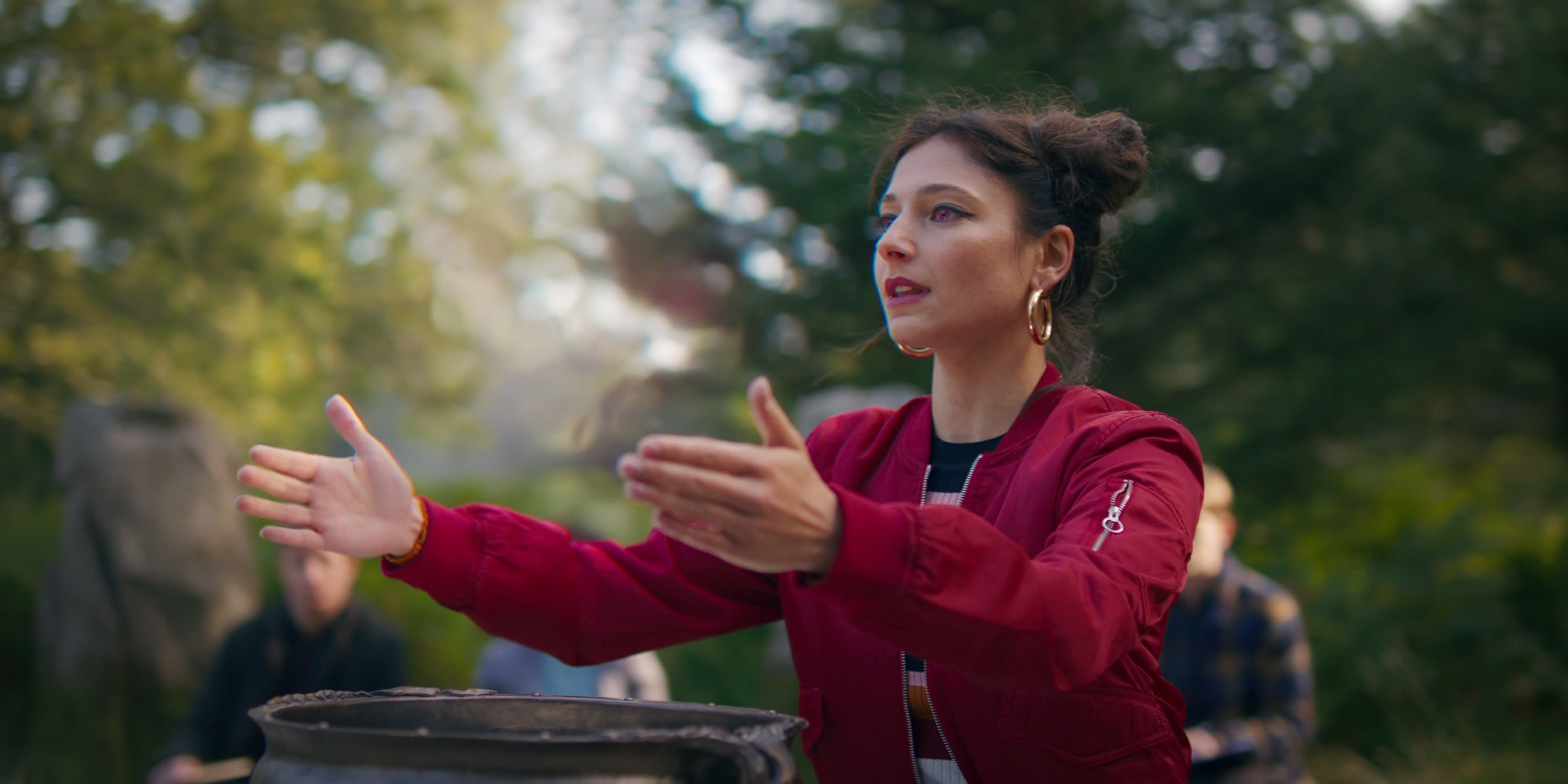 Musa, played by Elisha Applebaum, raising her arms in the forest