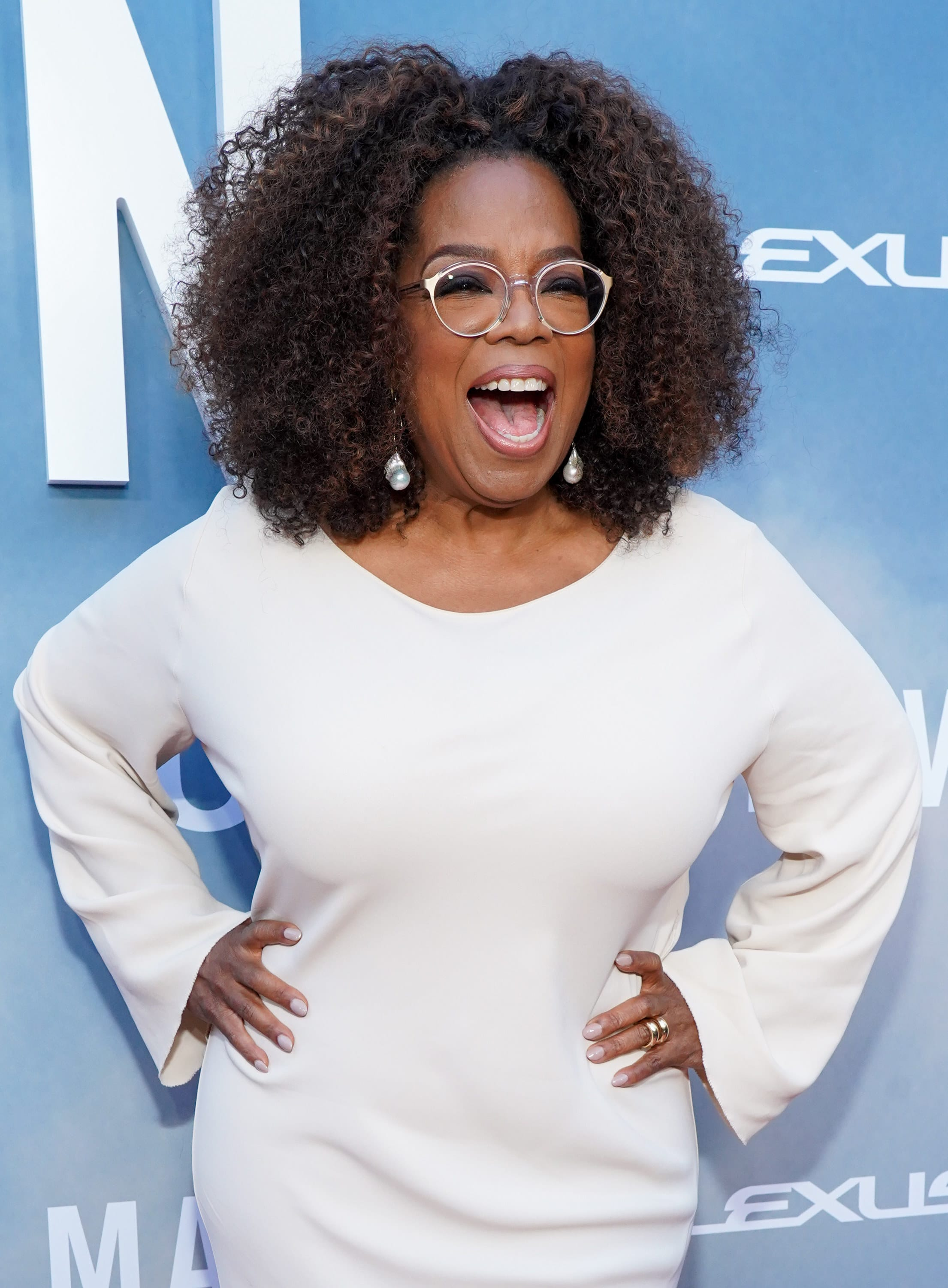 Oprah stands at a red carpet event with her hands on her hips