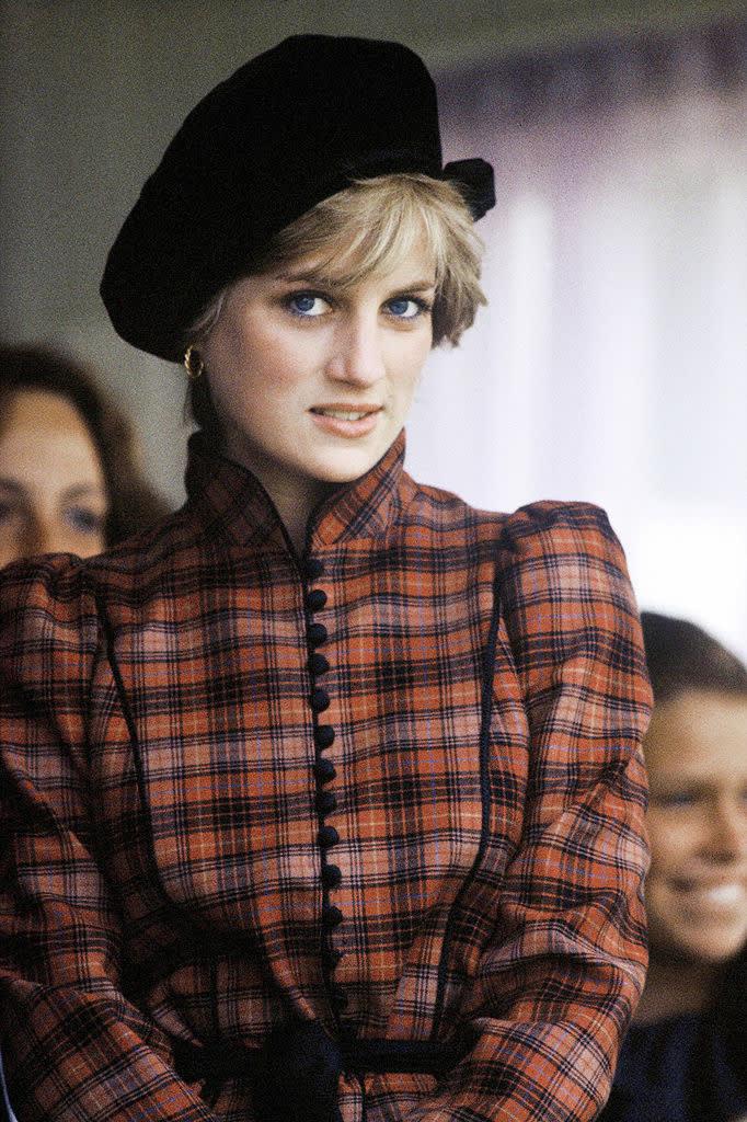 Diana com uma jaqueta xadrez de mangas volumosas.