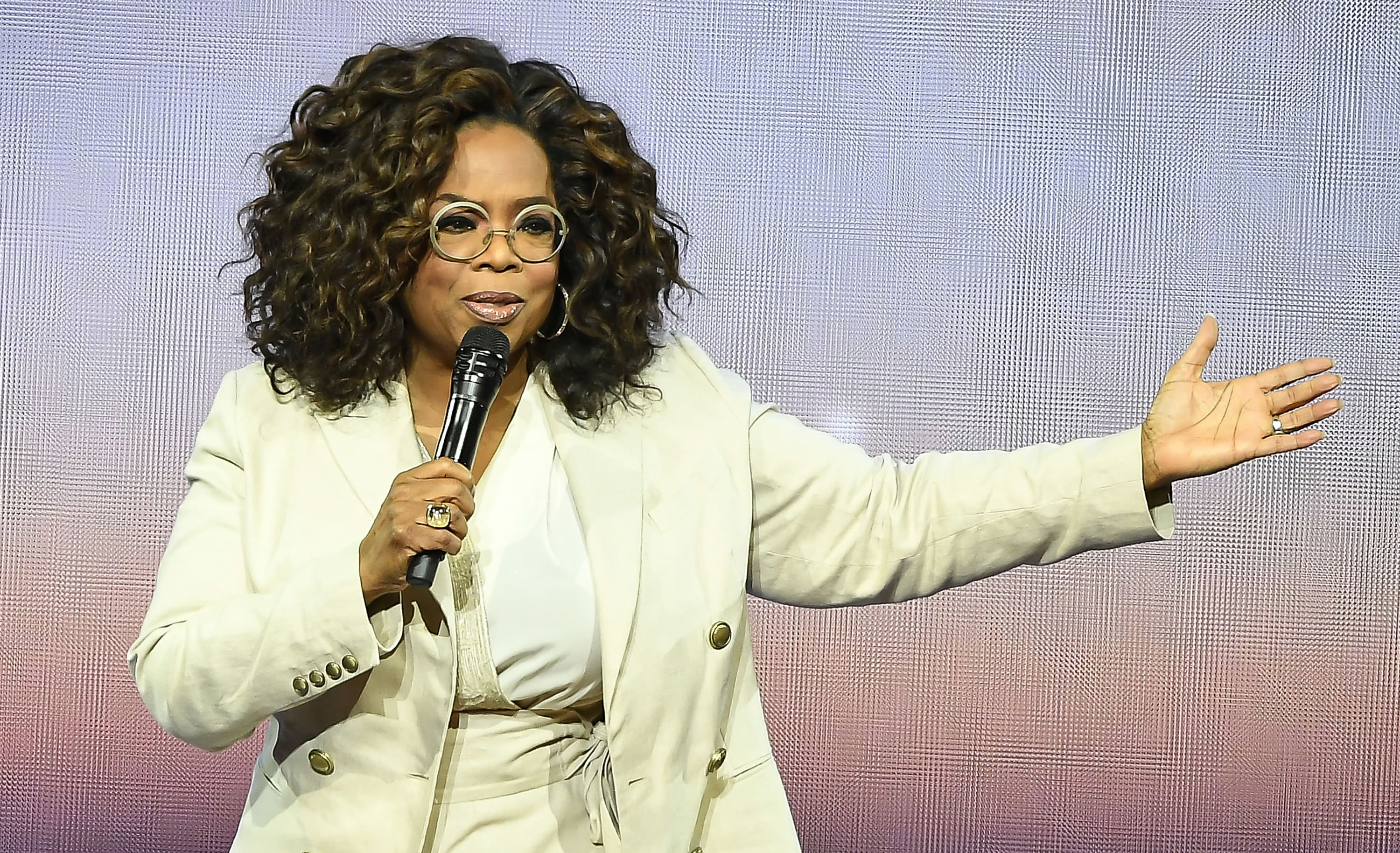 Oprah with her arm out as she talks into a microphone