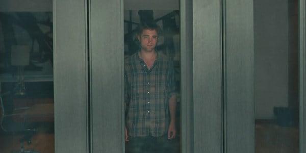 Imagem de Robert Pattinson atrás de uma porta de vidro.