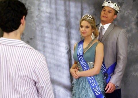 """Hannah com a faixa de rainha e uma coroa, abraçada por trás pelo namorado em """"Pretty Little Liars"""""""