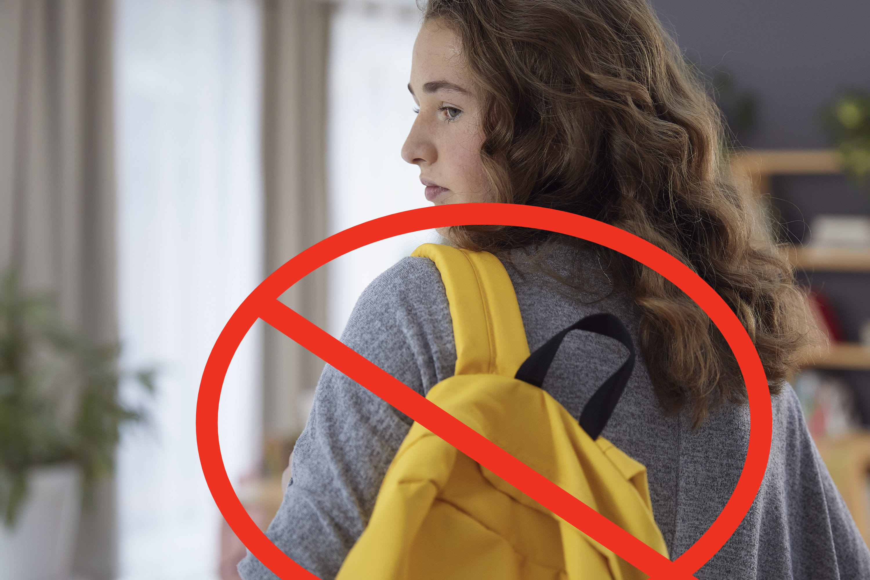 A teen carrying a backpack with a circle and line crossing it out superimposed upon the image