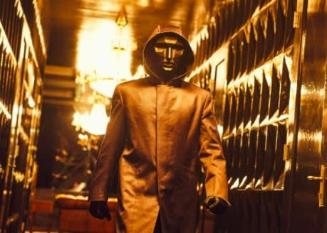 The Front Man in his black mask walks down a hallway