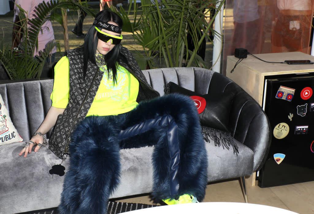 Billie com uma calça azul felpuda, camiseta verde neon e colete da Louis Vuitton sentada no sofá