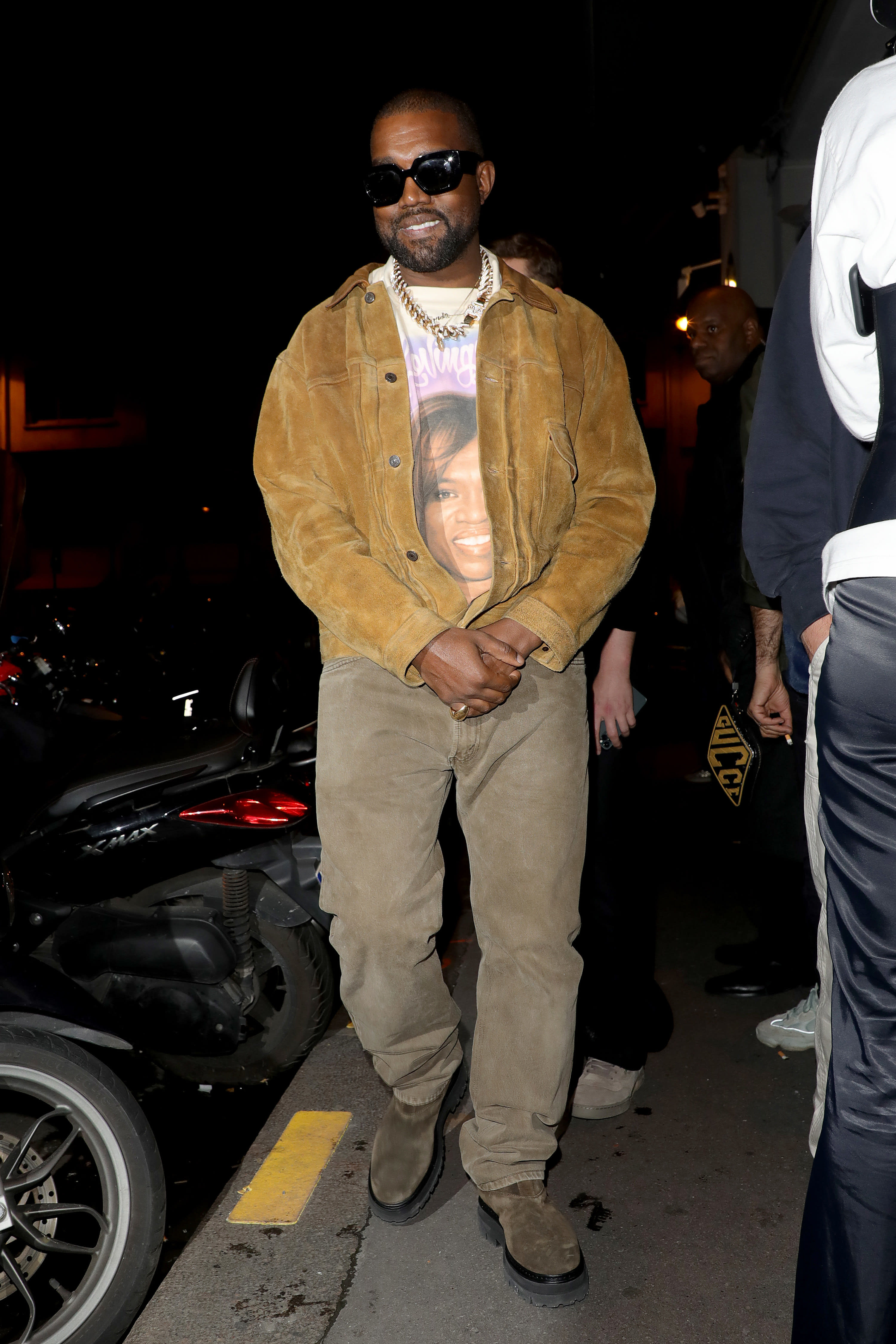 Kanye wears a graphic tee underneath a corduroy jacket and matching corduroy pants.